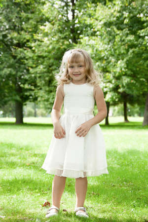 Smiling little girl in white dress standing in the park