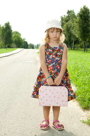 Girl standing alone on the roadside photo