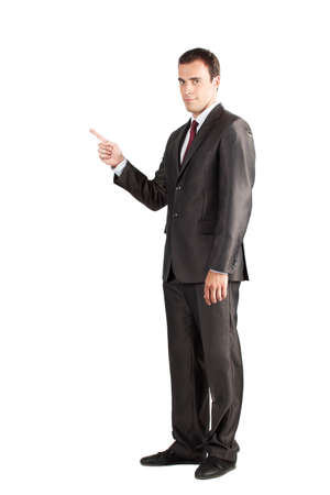 Full length of young business man in suit pointing at copy space over white background Stock Photo