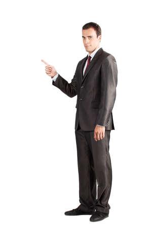 finger pointing: Longitud total de joven hombre de negocios en traje apuntando al espacio de la copia m�s de fondo blanco