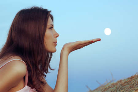 Beautiful brunette blows the moon with palm. Close-up
