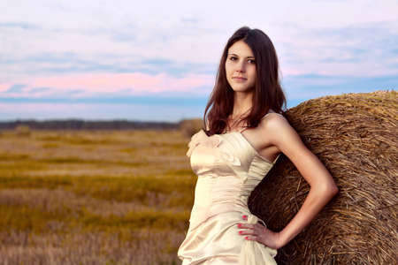 Beautiful bride posing in autumn field at sunset photo