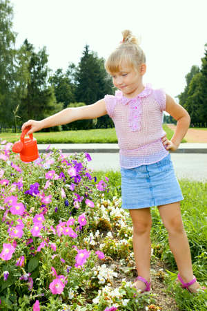 Cute little girl watering flowers in the park photo