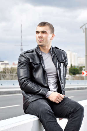 Beautiful strong young man sitting alongside a road photo