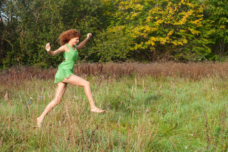 Young beautiful sexy girl in a green dress runs on a glade Stock Photo - 15480872