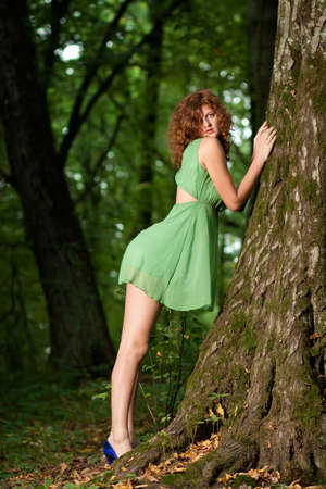 beckon: Sexy young beautiful red haired girl standing near the tree