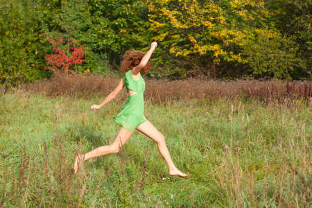 Young beautiful sexy girl in a green dress runs on a glade photo