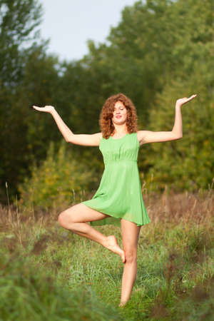 Young woman doing yoga moves, or meditating on the morning meadow photo