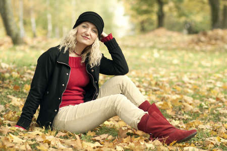 Beautiful caucasian young woman sitting on autumn leafs in park photo