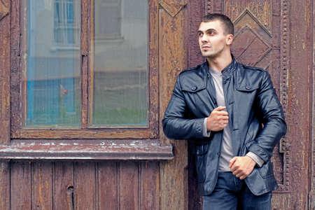 chaqueta de cuero: retrato de un hombre brutal joven con una chaqueta de cuero