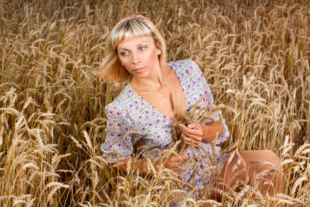 beautiful woman sitting on wheat field at sunset photo
