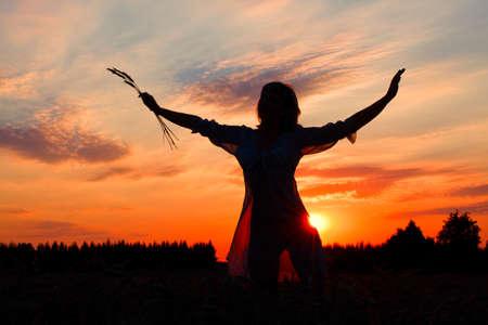 Silhouette di una donna snella giovane contro il cielo della sera Archivio Fotografico - 15919883