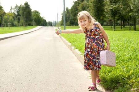descubridor: Niña hermosa en la carretera esperando un coche Foto de archivo