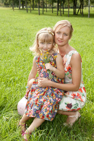 Cute mother and her daughter on summer meadow photo