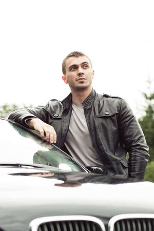 Young modern successful beautiful man standing near by his car  photo