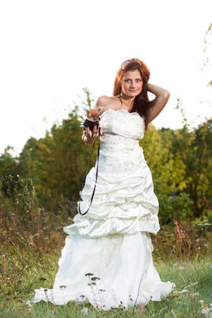 attractive young brunette bride with chihuahua dog photo