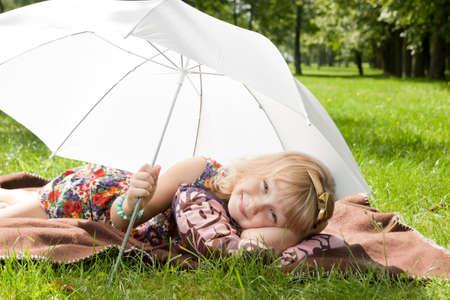 blithe: Ni�a que pone en la hierba bajo el paraguas Foto de archivo