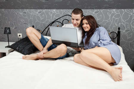 happy young beautiful couple with the laptop in bed at home photo