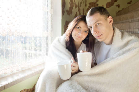 young couple drinking coffee in the morning and laughs at his home photo