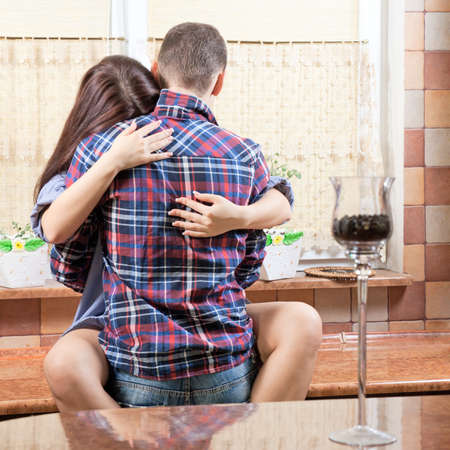 Portrait of a young couple embracing each-other in the kitchen  Archivio Fotografico