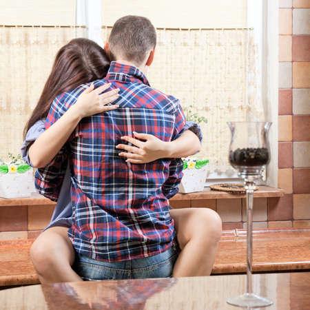Ritratto di una giovane coppia che abbraccia l'un l'altro in cucina Archivio Fotografico - 16518798