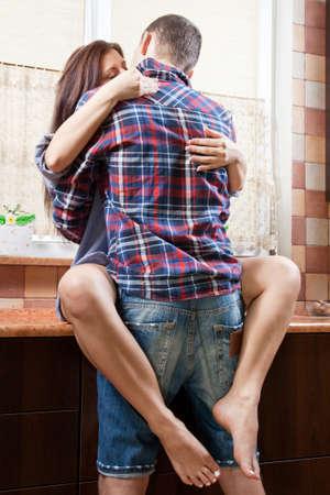 sexo pareja joven: Retrato de una joven pareja abraz�ndose en la cocina Foto de archivo