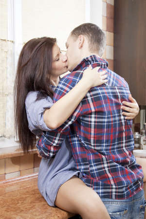 Portrait of a young couple embracing each-other in the kitchen