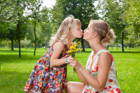 Beautiful girl kissing her mother in the park photo