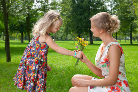 girl gives a bouquet of wild flowers to her mother photo