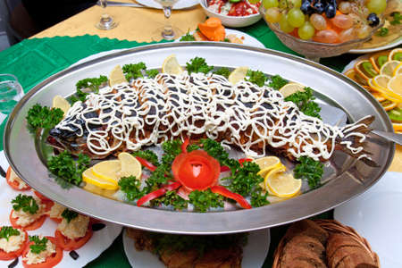 dog salmon: Large stuffed pink salmon with vegetables on the table