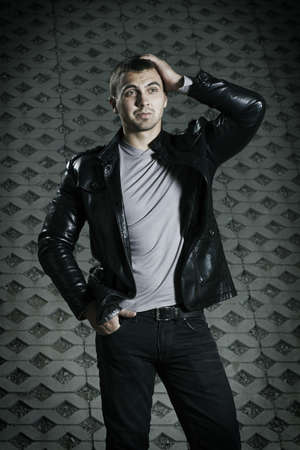 portrait of the brutal young man in a leather jacket photo