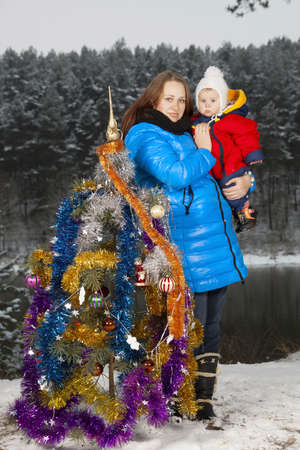 Mother and kid decorating Christmas tree outdoors photo