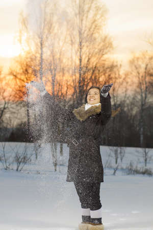Beautiful woman playing with snow in park on sunrise Stock Photo - 17049847