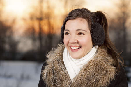 ear muffs: Beautiful smiling brunette girl with ear muffs in winter park Stock Photo