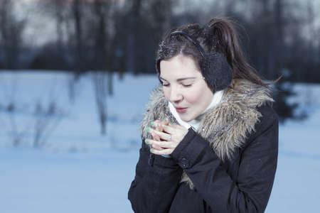 Woman hands warm breath in winter park Banco de Imagens