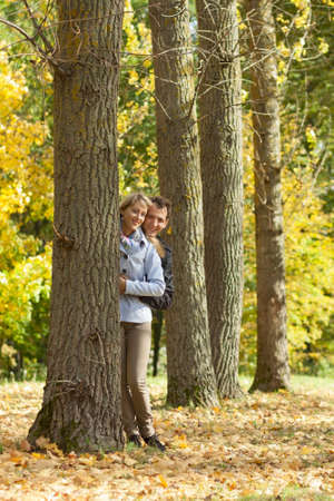 Portrait of a young couple hiding beyond the trees photo