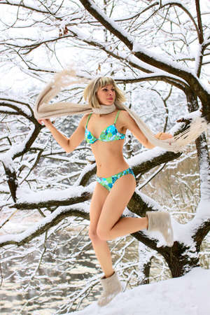 Blonde woman jumping on the snow in winter forest Stock Photo