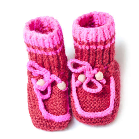 sweet stuff: Knitted baby footwear on a white background.