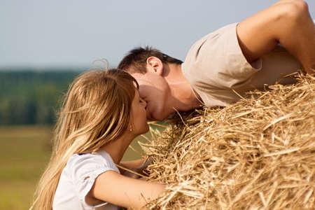 femme romantique: Jeune couple s'embrassant sur une botte de foin sur le champ récolté Banque d'images