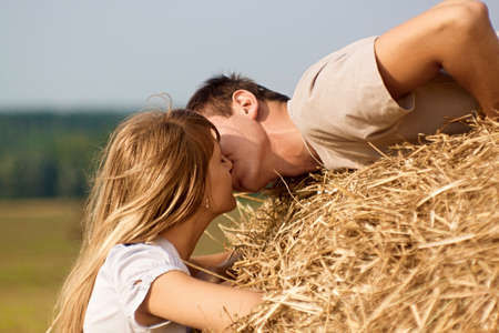 cute young farm girl: Young couple kissing on a haystack on harvested field