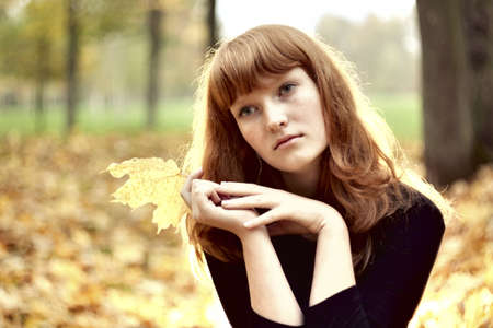 Beautiful redhaired girl sitting alone in autumn park photo