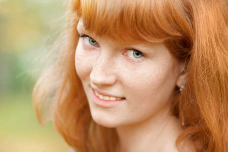 freckles: Portrait of young beautiful red-haired woman. Close up.