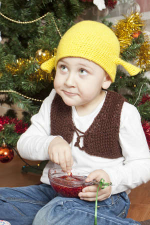 Funny boy eating jam sitting under the christmas tree photo