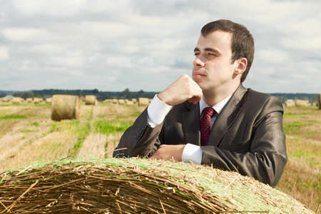 A business man in a suit is based on the stack of hay Stock Photo - 17499841