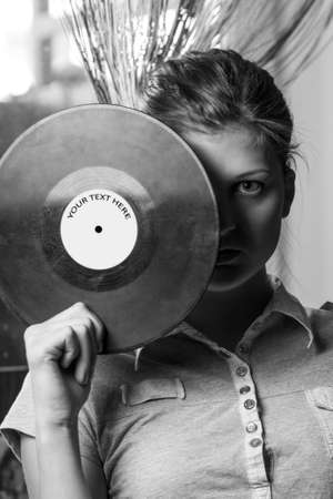 Girl covers her face with a vinyl disc. Grayscale. photo