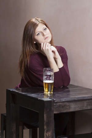 lonely girl sitting at a table in the bar photo