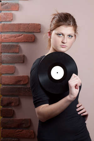 Portrait of beautiful girl with vinyl disc in her hand photo