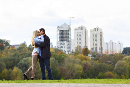 Happy couple kissing against building new brick house photo