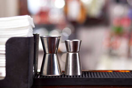 Two different jiggers and stand with napkins on bar photo