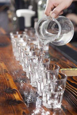 Bartender verter vasos de agua del jarro de cristal